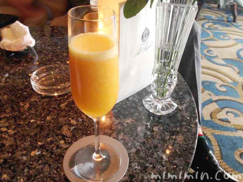 マンゴージュースとシャンパンのカクテル スカイラウンジ コンパスローズの写真
