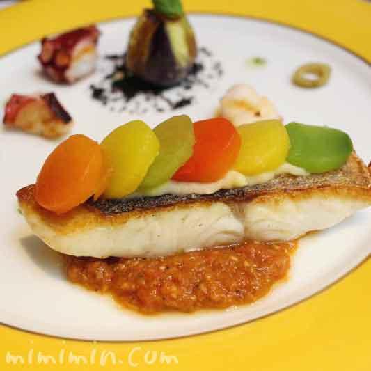パプリカのラメルを乗せたスズキのポワレ タコと魚介のトマト煮込み プロヴァンス風の写真