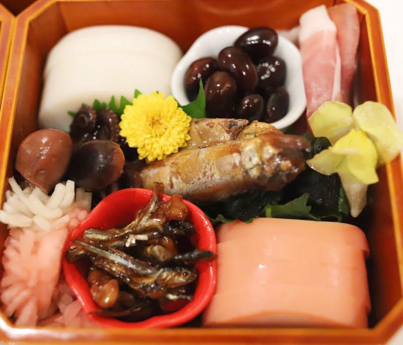 かまぼこと黒豆と生ハムとタコと鮎と昆布巻きとカブラの酢漬けとくるみ入り田作りの画像